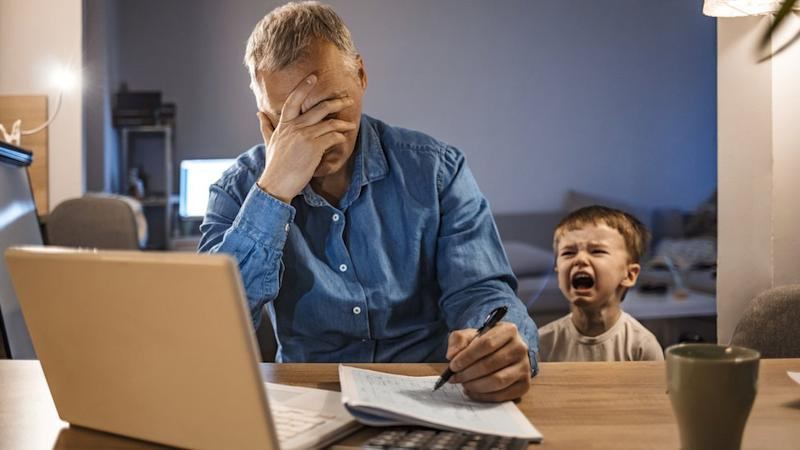 Man with head in hands in front of a laptop as toddler cries