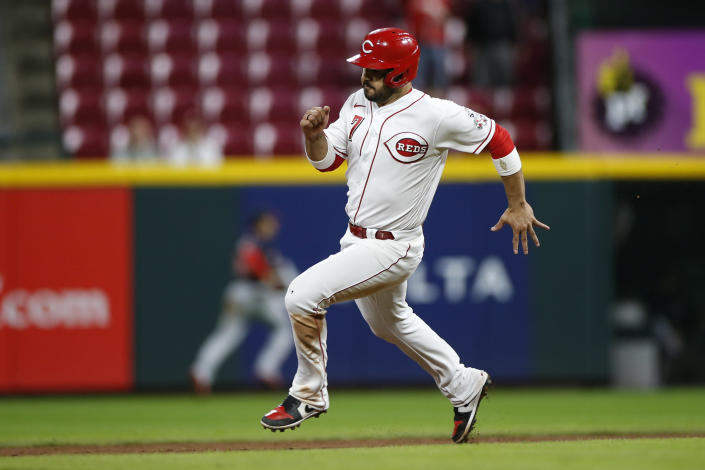 Cincinnati Reds' Eugenio Suarez scores from first base after Max Schrock hit a triple against the Washington Nationals during the ninth inning of a baseball game Thursday, Sept. 23, 2021, in Cincinnati. The Nationals beat the Reds 3-2. (AP Photo/Jay LaPrete)
