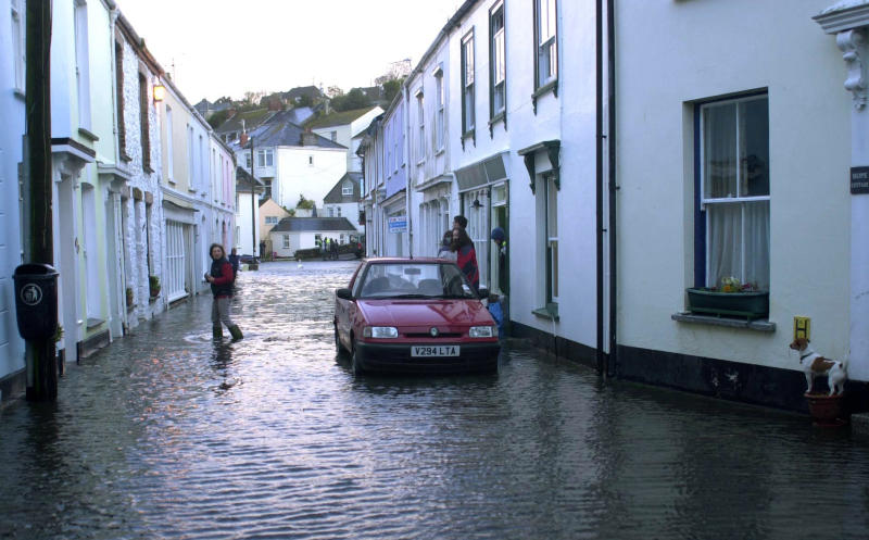 Residents walk through the flooded village of Flushing, Cornwall, south western England March 10, 2008. A storm rushing in from the Atlantic lashed the south west on Monday as high winds and tides brought the risk of coastal flooding. REUTERS/Paul Armiger (BRITAIN)