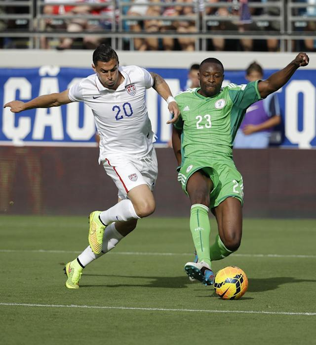 United States's Geoff Cameron (20) tries to stop Nigeria's Shola Ameobi (23) as he takes a shot on goal during the first half of an international friendly soccer match in Jacksonville, Fla., Saturday, June 7, 2014. (AP Photo/John Raoux)