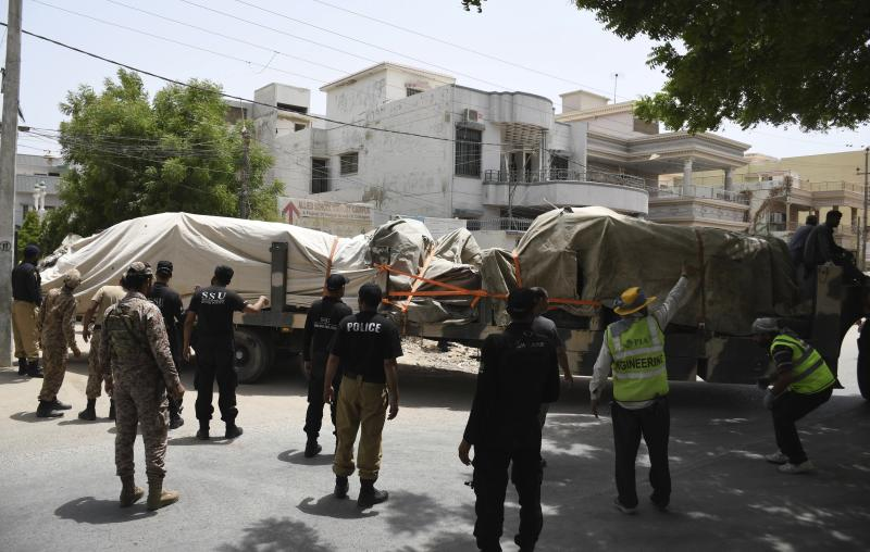 Pakistani security personnel stand guard near trucks carrying the wreckage of a Pakistan International Airlines plane from the crash site, Thursday, May 28, 2020 in Karachi, Pakistan. (AP Photo/Fareed Khan)