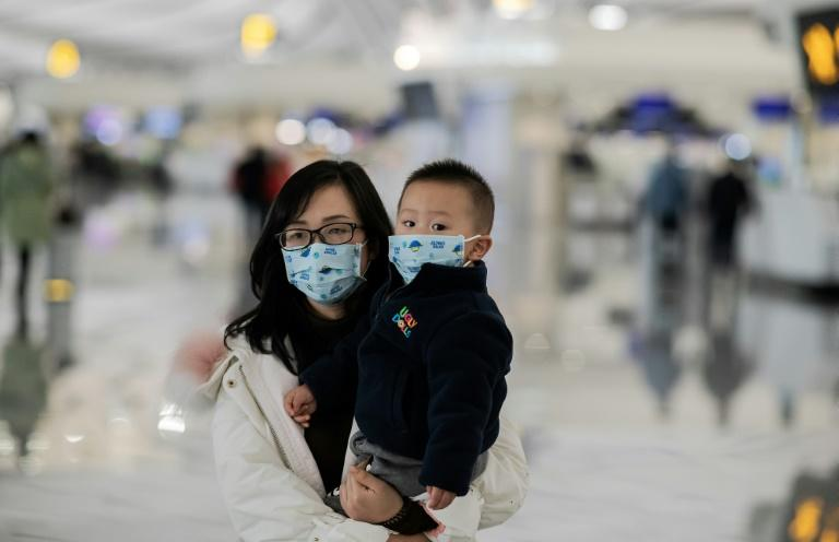 A woman and her child walk toward the check-in counter at Daxing international airport in Beijing