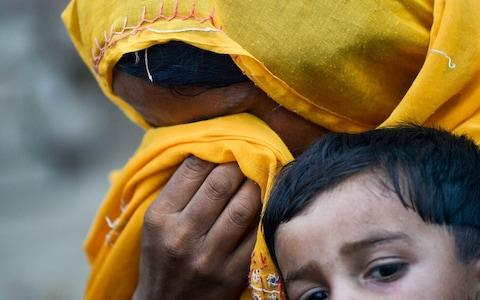 a Pakistani woman cries in her scarf as she holds her HIV infected child outside a house at Wasayo village in Rato Dero - Credit: AFP