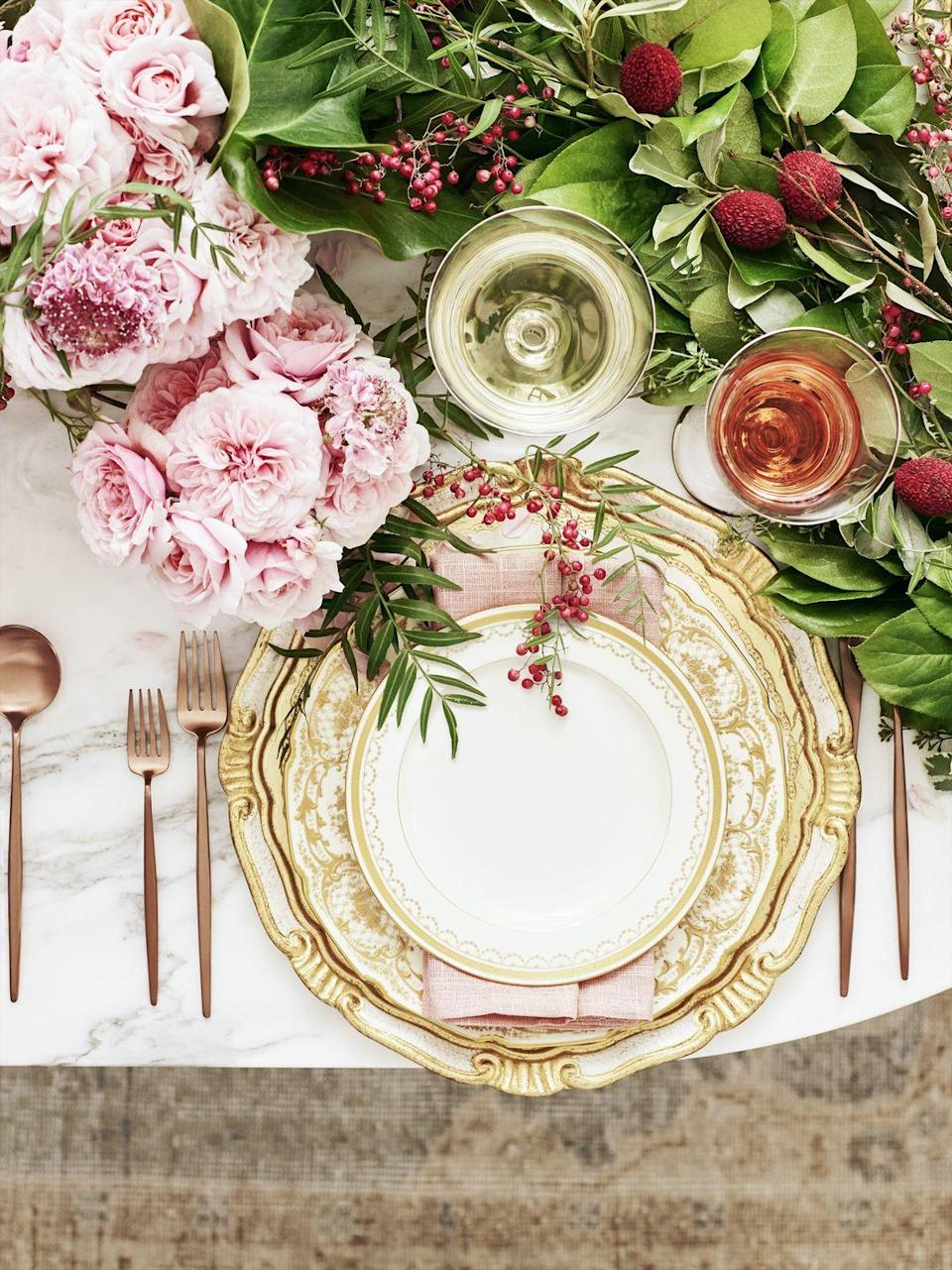 """<p>Break out the fine china, or put one gilded salad plate atop an everyday set to make each place setting feel special. A runner of greenery and blooms is a low-profile floral option that's easy for guests to chat over.</p><p><span class=""""redactor-invisible-space""""><span class=""""redactor-invisible-space""""><a class=""""link rapid-noclick-resp"""" href=""""https://go.redirectingat.com?id=74968X1596630&url=https%3A%2F%2Fwww.etsy.com%2Flisting%2F470626436%2Ffreshly-harvested-seeded-eucalyptus&sref=https%3A%2F%2Fwww.goodhousekeeping.com%2Fholidays%2Fchristmas-ideas%2Fhow-to%2Fg2196%2Fchristmas-table-settings%2F"""" rel=""""nofollow noopener"""" target=""""_blank"""" data-ylk=""""slk:SHOP FRESH RUNNERS"""">SHOP FRESH RUNNERS</a></span></span><br></p>"""