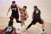 Miami Heat guard Goran Dragic (7) battles for the ball against Washington Wizards guard Raul Neto, center, during the first half of an NBA basketball game, Saturday, Jan. 9, 2021, in Washington. Heat forwards Kelly Olynyk (9) and Jimmy Butler (22) look on. (AP Photo/Nick Wass)