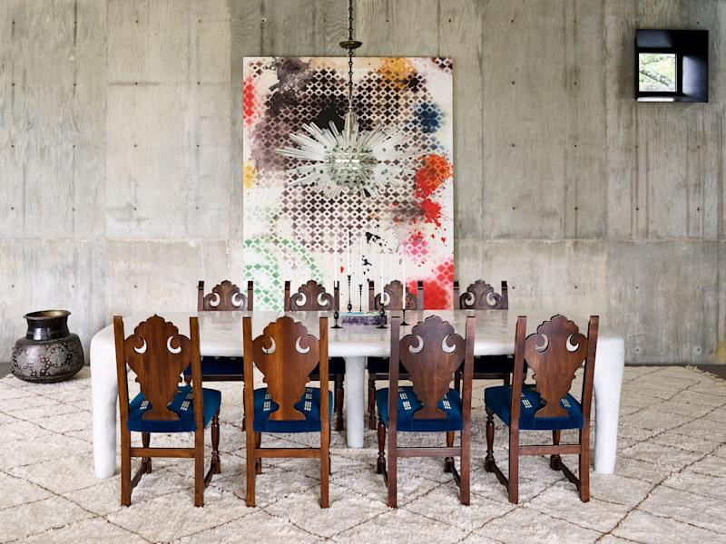 """""""Suzanne wanted the interiors to feel artful yet function for her children,"""" says Vaughn Miller. She and McFayden worked with Korean artist Hun-Chung Lee, in partnership with R & Company, to create a minimalist ceramic dining table that offsets the antique chairs, ornate Bakalowits chandelier, and vibrant artwork by Ida Tursic and Wilfried Mille."""