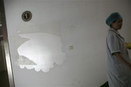 A medical staff walks past the remains of a Mead Johnson infant formula advertisement stuck on a wall at the corner of a staircase inside Hangzhou Tianmushan hospital, Zhejiang province, September 26, 2013. REUTERS/Chance Chan
