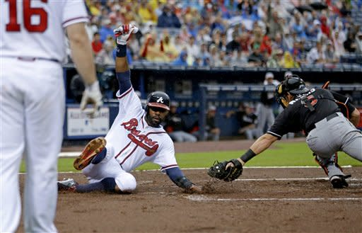 Atlanta Braves' Jason Heyward, left, beats the tag by Miami Marlins catcher Jeff Mathis to score off a single by teammate Freddie Freeman in the first inning of a baseball game, Thursday, July 4, 2013, in Atlanta. (AP Photo/David Goldman)