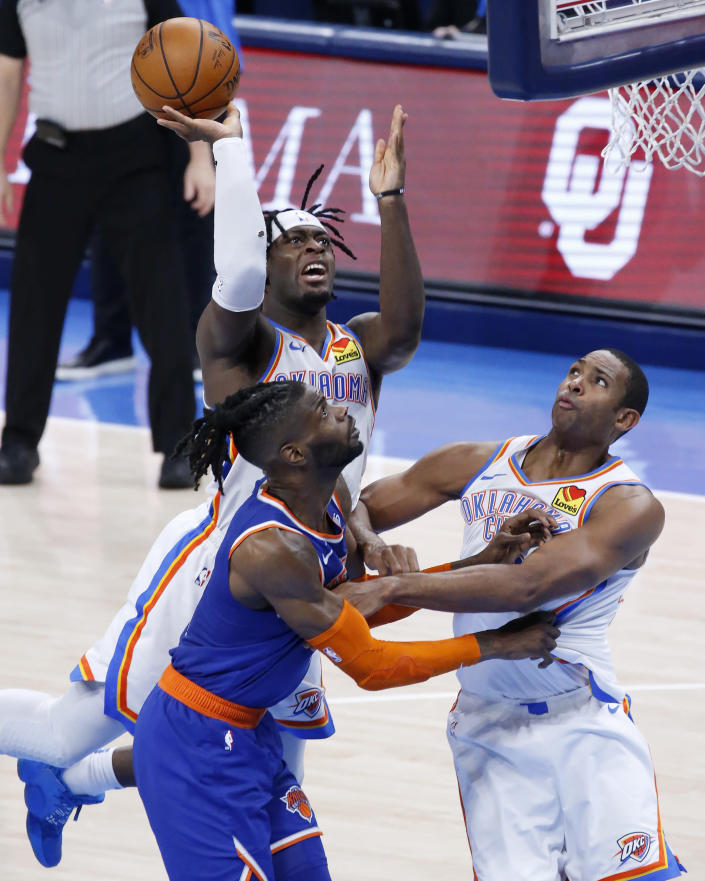Oklahoma City Thunder forward Luguentz Dort (5) takes a shot against New York Knicks center Nerlens Noel (3), guarded by Oklahoma City Thunder center Al Horford (42), during the first half of an NBA basketball game, Saturday, March 13, 2021, in Oklahoma City. (AP Photo/Garett Fisbeck)