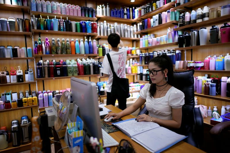 Deng Jinling, manager of Lucky Bird Trade Co. checks her online store on a company at a cup products shop at the Yiwu Wholesale Market following an outbreak of the novel coronavirus disease (COVID-19), in Yiwu