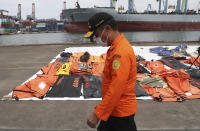 An Indonesian rescue team walk near debris found in the waters around the location where a Sriwijaya Air passenger jet crashed at the search and rescue command center at Tanjung Priok Port in Jakarta, Indonesia, Friday, Jan 15, 2021. More searchers and rescuers joined the search Friday for wreckage and victims from an Indonesian plane that crashed last weekend in the Java Sea. (AP Photo/Achmad Ibrahim)