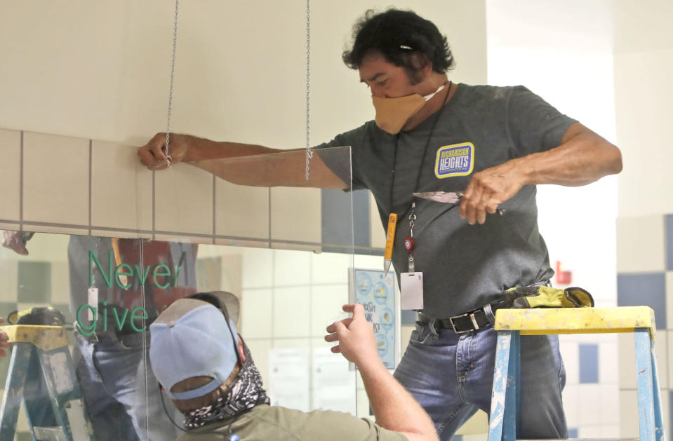 Richardson Independent School District workers Daniel Limon, right, and Matt Attaway install a plexiglass barrier in the restroom at Bukhair Elementary School in Dallas, Wednesday, July 15, 2020. Texas Education Commissioner Mike Morath told the state Board of Education on Tuesday that the annual State of Texas Assessments of Academic Readiness, also known as STAAR, will return in the 2020-2021 school year. (AP Photo/LM Otero)