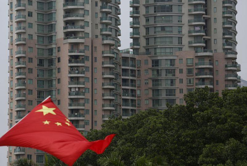 A Chinese national flag flutters in front of an apartment tower in the southern Chinese city of Shenzhen