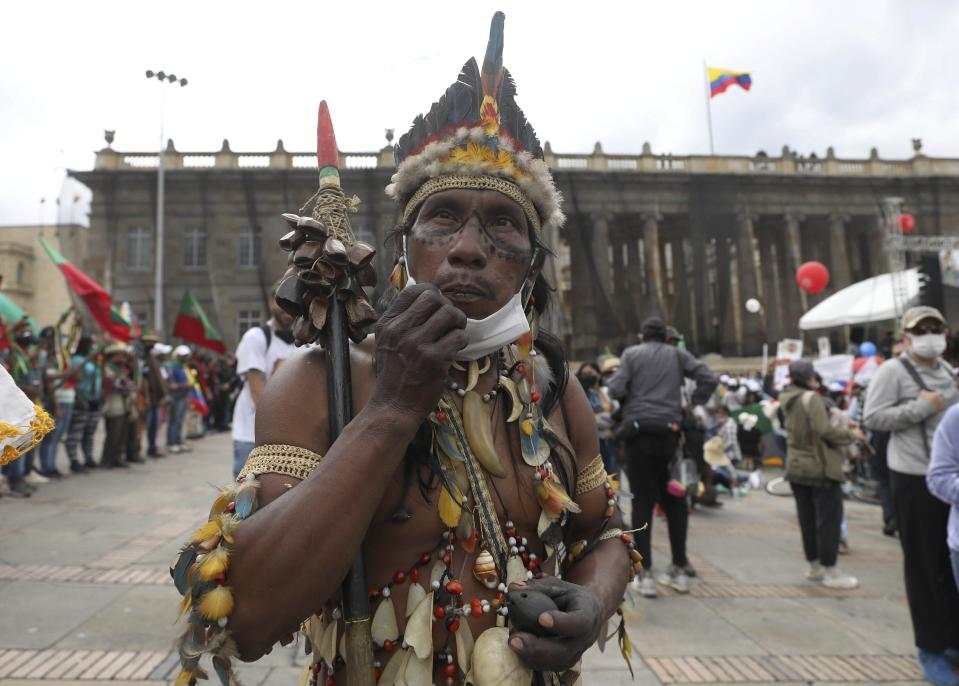 An Indigenous man arrives to Plaza Bolivar to take part in a demonstration against the government's handling of a wide range of issues including the economic fallout of the pandemic and implementation of the peace accord, in Bogota, Colombia, Wednesday, Oct. 21, 2020. Indigenous leaders, students and union members gathered at in the historic square waving flags and banners decrying the government nearly one year after massive protests rocked the country only to fizzle with little to show by way of reform. (AP Photo/Fernando Vergara)