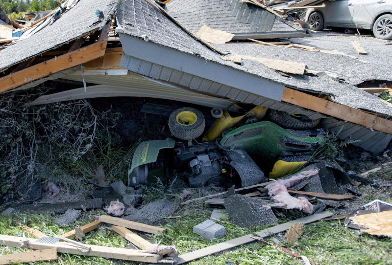 A ride-on lawnmower lies under a collapsed roof in a neighbourhood destroyed by a tornado in Dunrobin, Ont., west of Ottawa, on Saturday, Sept. 22, 2018. The storm tore roofs off of homes, overturned cars and felled power lines in the Ottawa community of Dunrobin and in Gatineau, Que. THE CANADIAN PRESS/Justin Tang