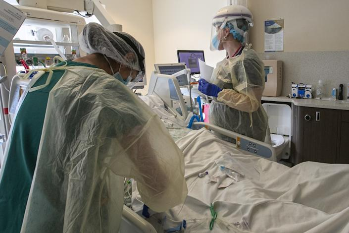 Two health workers in gowns, masks and face shields stand on either side of a patient bed