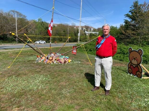 """Wayne Hall and other Scout members built a """"floating flagpole"""" with the flag at half mast as a temporary memorial to 5-year-old Max Thomas."""