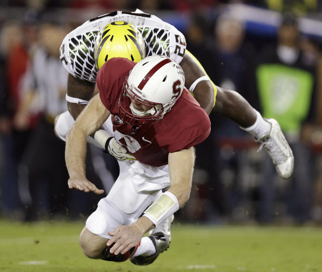 Oregon linebacker Derrick Malone (22) tackles Stanford quarterback Kevin Hogan after Hogan passed the ball during the first quarter of an NCAA college football game in Stanford, Calif., Thursday, Nov. 7, 2013. (AP Photo/Marcio Jose Sanchez)