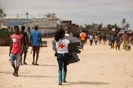 Volunteer from the Mozambique Red Cross carries supplies for survivors of Cyclone Idai, at an evacuation centre in Beira, Mozambique, March 21, 2019. Denis Onyodi/Red Cross Red Crescent Climate Centre/Handout via REUTERS