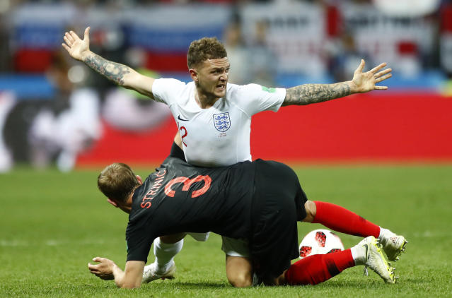 England's Kieran Trippier, up, and Croatia's Ivan Strinic challenge for the ball during the semifinal match between Croatia and England at the 2018 soccer World Cup in the Luzhniki Stadium in Moscow, Russia, Wednesday, July 11, 2018. (AP Photo/Matthias Schrader)
