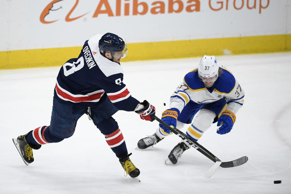 Washington Capitals left wing Alex Ovechkin (8) shoots the puck past Buffalo Sabres center Casey Mittelstadt (37) during the second period of an NHL hockey game Thursday, April 15, 2021, in Washington. (AP Photo/Nick Wass)