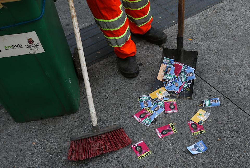 SAO PAULO, BRAZIL - NOVEMBER 15: A garbage man sweeps the street full of political pamphlets during municipal elections day on November 15, 2020 in Sao Paulo, Brazil. In Sao Paulo, 13 candidates are running for mayor, and about 2,000 candidates compete for one of the 55 vacancies in the Chamber for Councilman. (Photo by Alexandre Schneider/Getty Images)