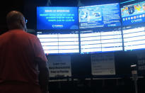 A gambler checks the odds boards at the FanDuel sportsbook in East Rutherford N.J. on Aug. 30, 2021. Tyhe American Gaming Association says 45.2 million Americans plan to bet on NFL games this season, up 36% from last year. (AP Photo/Wayne Parry)
