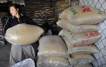A worker carries a sack of soybeans at a food wholesale market in Shenyang