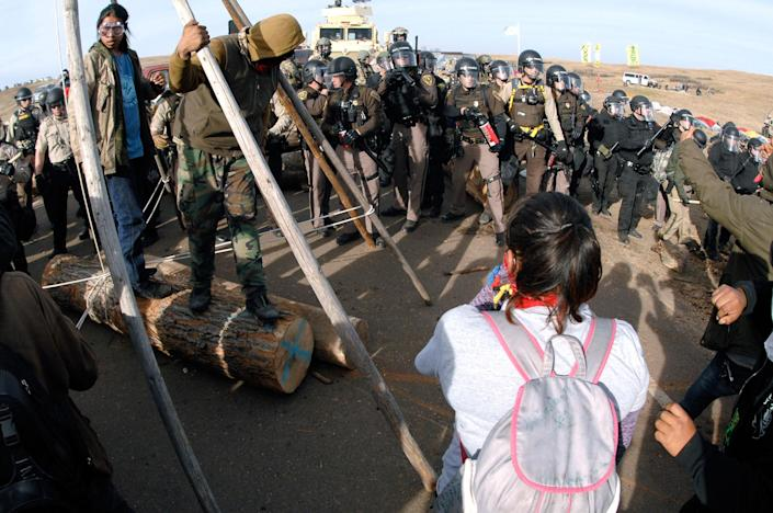 <p>Protesters in the left foreground shield their faces as a line of law enforcement officers holding large canisters with pepper spray shout orders to move back during a standoff in Morton County, N.D., Thursday, Oct. 27, 2016. (Photo: Mike McCleary/The Bismarck Tribune via AP) </p>