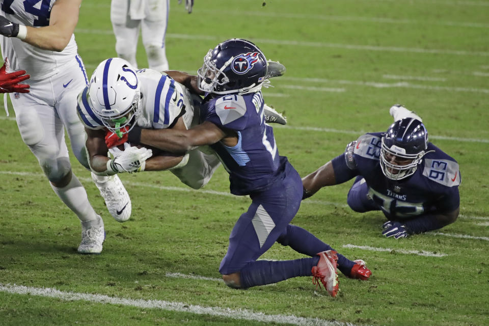 Indianapolis Colts running back Nyheim Hines, left, dives past Tennessee Titans cornerback Malcolm Butler, center, for a touchdown. (AP Photo/Ben Margot)