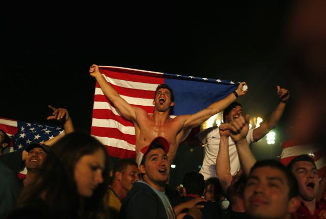 U.S. soccer fans celebrate at the end of the 2014 World Cup soccer match between U.S. and Ghana, which was broadcast on a large screen at Copacabana beach, in Rio de Janeiro, June 16, 2014. REUTERS/Pilar Olivares (BRAZIL - Tags: SPORT SOCCER WORLD CUP)