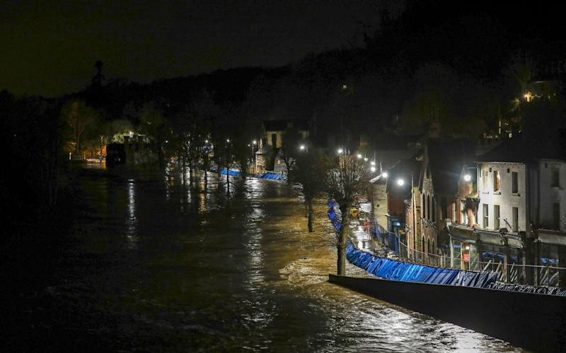Temporary flood barriers hold back the river Severn in Ironbridge, Shropshire - PA