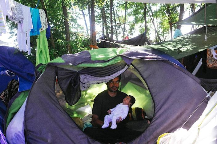 A man holds his baby in a tent at a migrant camp situated on the Serbia-Hungary border in Horgos (AFP Photo/Alexa Stankovic)