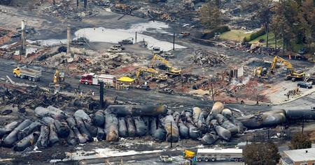 FILE PHOTO: Workers and firefighters work on the remains of downtown Lac Megantic