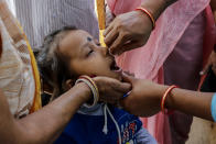 A child is administered polio vaccine at a booth in Kolkata, India, Sunday, Nov. 22, 2020. India's total number of coronavirus cases since the pandemic began has crossed 9 million. (AP Photo/Bikas Das)