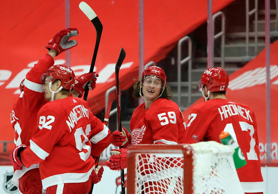Detroit Red Wings left wing Tyler Bertuzzi (59) celebrates with center Vladislav Namestnikov (92) and defenseman Filip Hronek (17) after scoring the game-winning goal in overtime to defeat the Columbus Blue Jackets in an NHL hockey game Tuesday, Jan. 19, 2021, in Detroit.