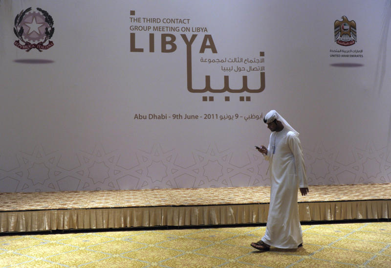 A man walks past the stage for the Libya Contact Group family photo at the Emirates Palace Hotel in Abu Dhabi, United Arab Emirates, Thursday, June 9, 2011.  (AP Photo/Susan Walsh, Pool)