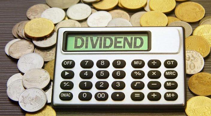 """A calculator projecting the word """"DIVIDEND"""" rests on a pile of gold and silver coins."""
