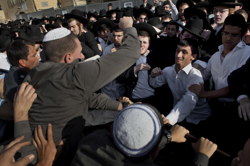 "Ultra-orthodox Jewish men scuffle with Israeli security forcers during a prayer organized by the ""Women of the Wall"" organization, not pictured, at the Western Wall, the holiest site where Jews can pray in Jerusalem's old city, Friday, May 10, 2013. The ""Women of the Wall"" group has been holding monthly prayer services on the first day of the Hebrew month at the Western Wall in Jerusalem for more than two decades, wearing prayer shawls and performing religious rituals reserved for men under Orthodox Judaism. Accused by ultra-Orthodox leaders of violating ""local custom"" at the holy site, many members have been arrested. On Friday the tables were turned because of the court ruling. Police protected the women and arrested three ultra-Orthodox men for disorderly conduct, police spokesman Micky Rosenfeld said. (AP Photo/Bernat Armangue)"