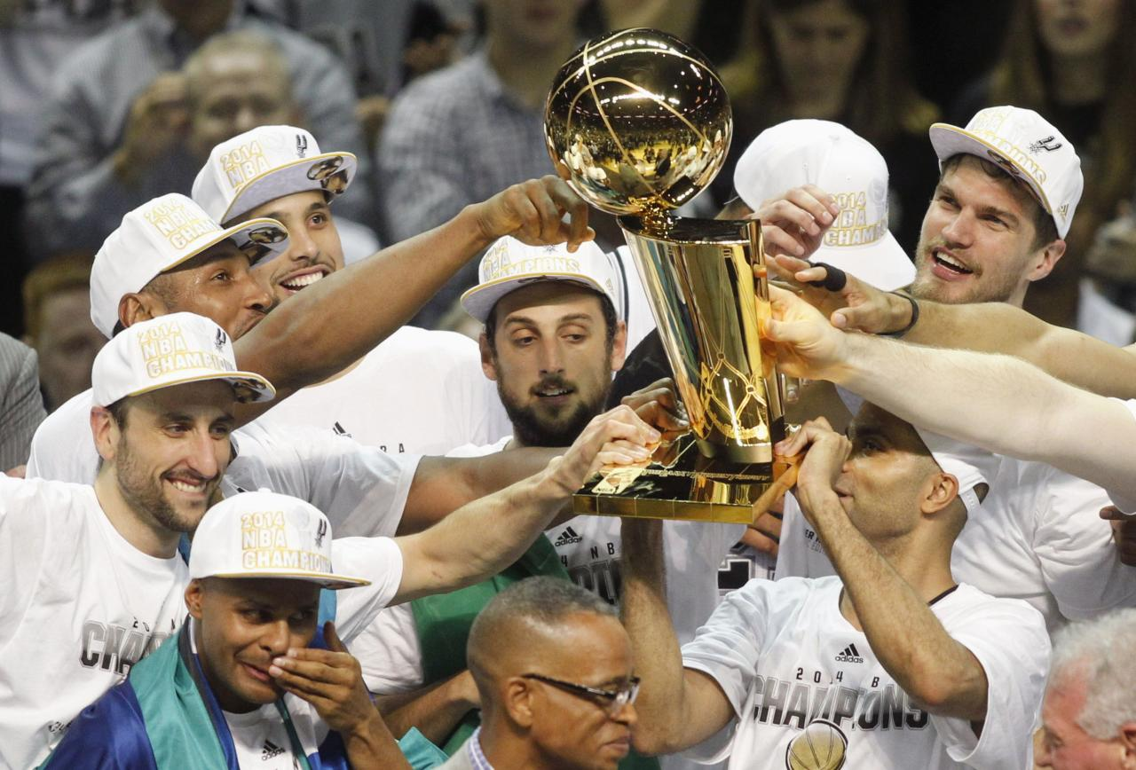 San Antonio Spurs' Patty Mills of Australia (bottom L) cries as teammates hoist the Larry O'Brien trophy after the Spurs defeated the Miami Heat in Game 5 of their NBA Finals basketball series in San Antonio, Texas, June 15, 2014. REUTERS/Mike Stone (UNITED STATES - Tags: SPORT BASKETBALL)
