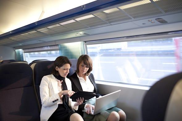 Two business women work on a train.