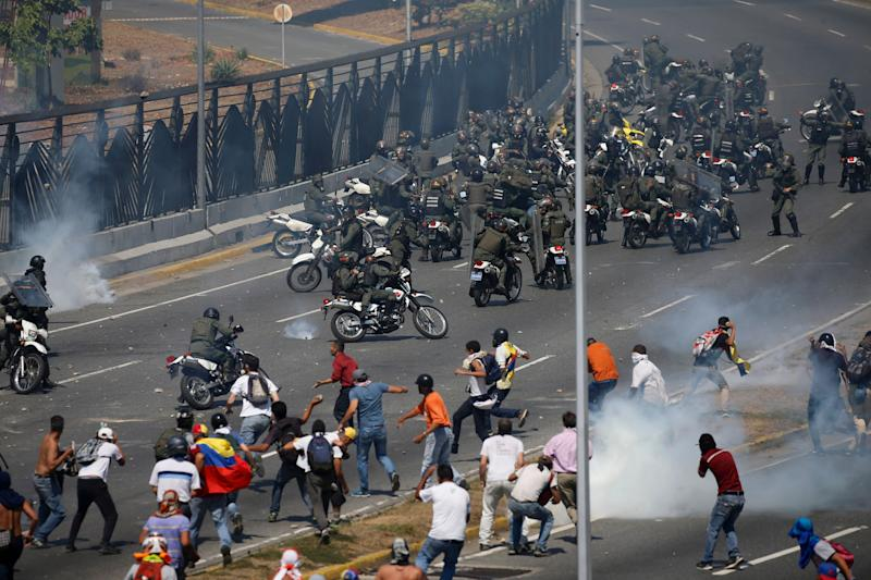 Opponents to Venezuela's President Nicolas Maduro confront loyalist Bolivarian National Guard troops firing tear gas at them, outside La Carlota military airbase in Caracas, Venezuela, Tuesday, April 30, 2019. (Photo: Fernando Llano/AP)