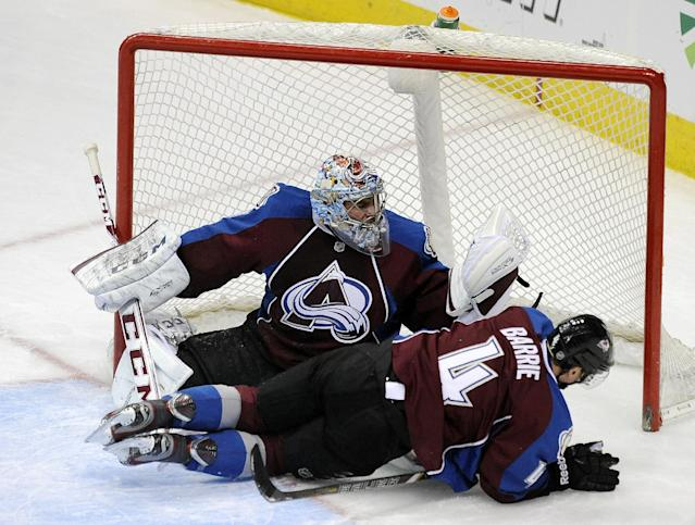 Colorado Avalanche defenseman Tyson Barrie, front, runs into Avalanche goalie Semyon Varlamov, of Russia, during the first period of an NHL hockey game against the Columbus Blue Jackets on Tuesday, Dec. 31, 2013, in Denver. (AP Photo/Chris Schneider)