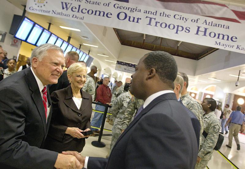 "FILE- In this Nov. 22, 2011 file photo, Gov. Nathan Deal, left, and wife Sandra greet Mayor Kasim Reed, right, as they unveil banners reading ""Welcome Our Troops Home"" at Hartsfield-Jackson International Airport in Atlanta. In this era of hyper-partisan rhetoric, the unique friendship that has developed between Deal and Reed has its roots in a shared interest in economic development and has blossomed into a powerful political alliance that is paying dividends. (AP Photo/David Goldman, File)"