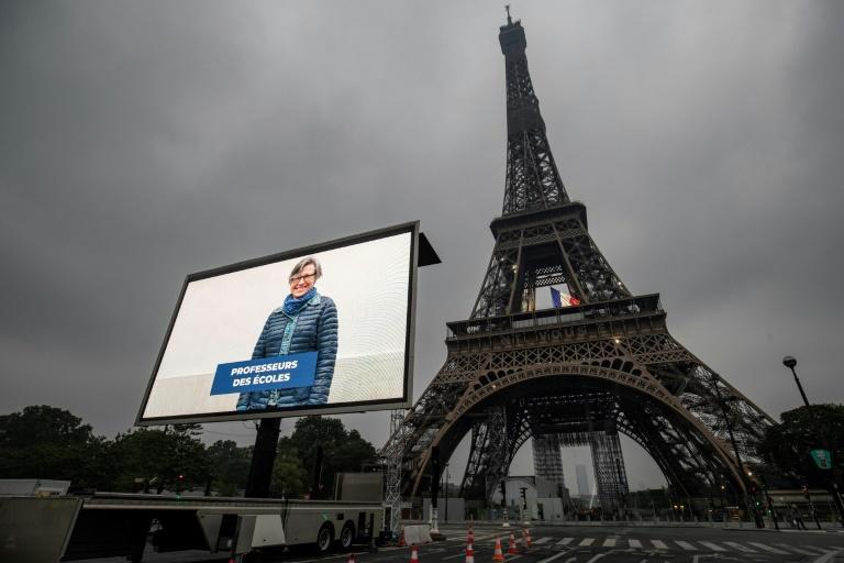 A portrait of a teacher who was mobilized during the pandemic is displayed on a giant screen in Paris on the eve of France's easing of lockdown measures