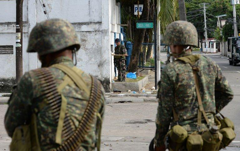 A policeman (C) uses a mirror to observe the position of enemy snipers as marines look on during the standoff between Muslim gunmen and army troops in Zamboanga City, on the southern island of Mindanao on September 10, 2013