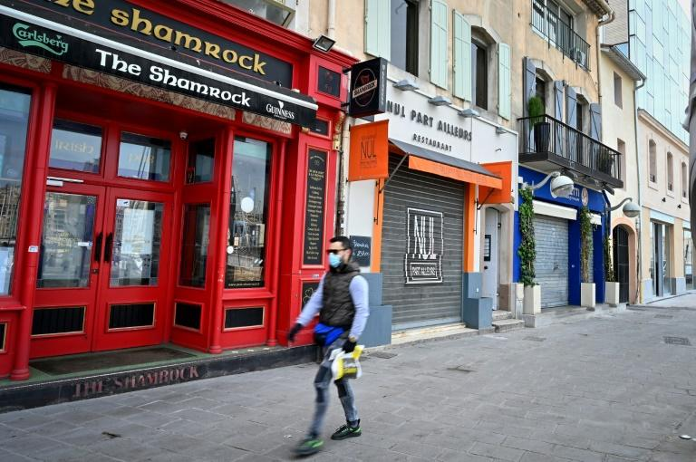 A man wearing a face mask walks past closed bars and restaurants in Marseille, southern France