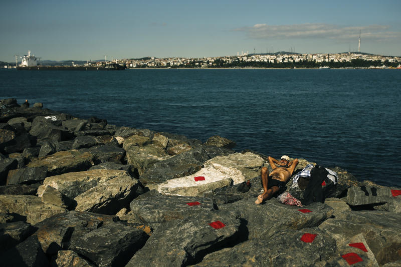 A man sunbathes during a four-day curfew declared by the government in an attempt to control the spread of coronavirus, outside Istanbul, Sunday, May 24, 2020. Turkey's senior citizens were allowed to leave their homes for a third time as the country continues to ease some coronavirus restrictions. (AP Photo/Emrah Gurel)