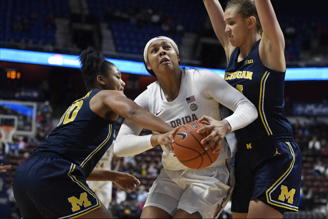 Florida State's Kiah Gillespie, center, is fouled by Michigan's Naz Hillmon, left, as Michigan's Izabel Varejo, right, defends in the second half of an NCAA college basketball game, Sunday, Dec. 22, 2019, in Uncasville, Conn. (AP Photo/Jessica Hill)