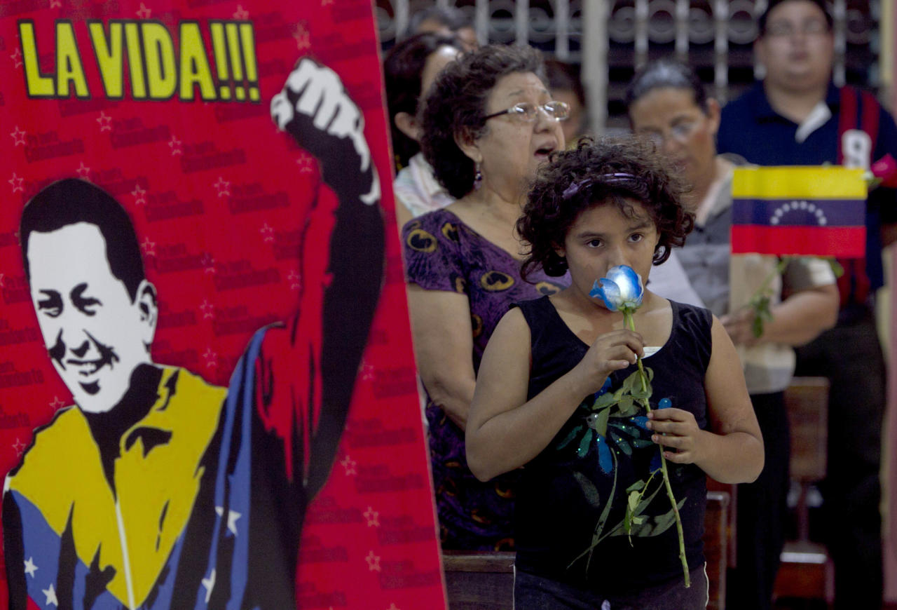 "A person holds a flower during a mass in support of Venezuela's President Hugo Chavez next to an image of him that reads in Spanish ""The life"" in Managua, Nicaragua, Thursday March, 1, 2012. Doctors successfully extracted a tumor from Chavez's pelvic region and he was stable and recovering in Cuba on Tuesday with family at his side, Venezuela's Vice President Elias Jaua said. (AP Photo/Esteban Felix)"